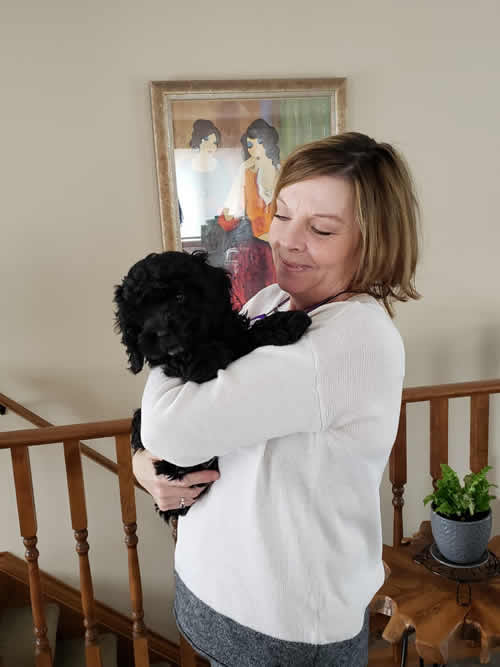 Black cockapoo George with owner